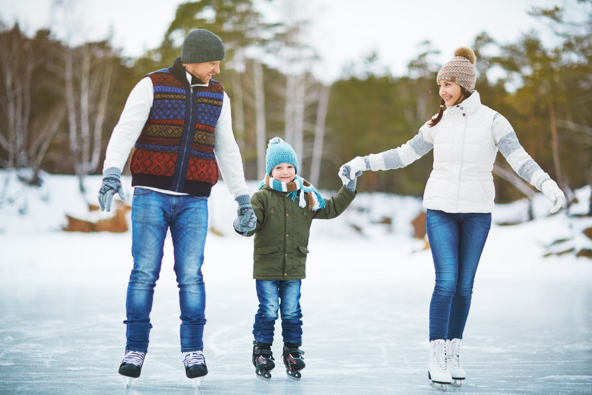 Young family holding hands and ice skating on rink