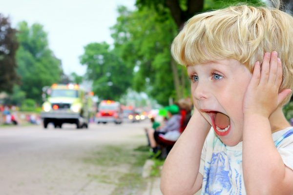 A young blonde boy covers his ears and looks excited as ambulances and fire trucks drive by in a parade.