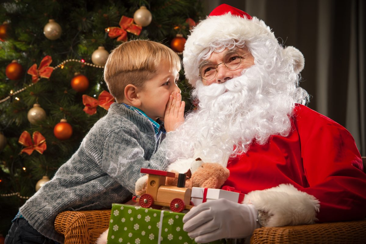 Little boy whispers to Santa Claus