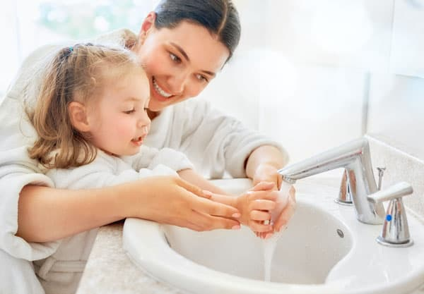 A mother and daugher wash hands together