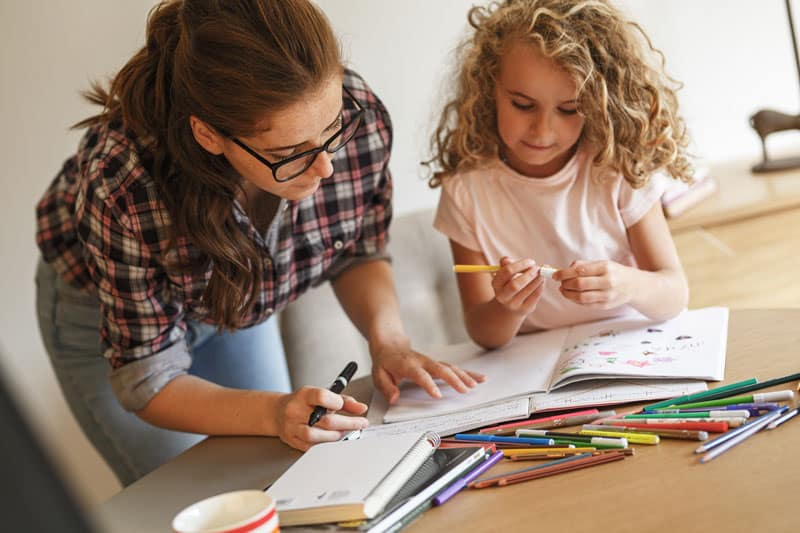 A mother helps her daughter with homework