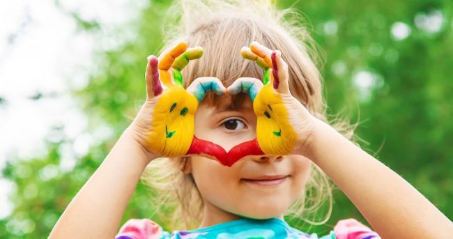 Little girl making a heart with her painted hands