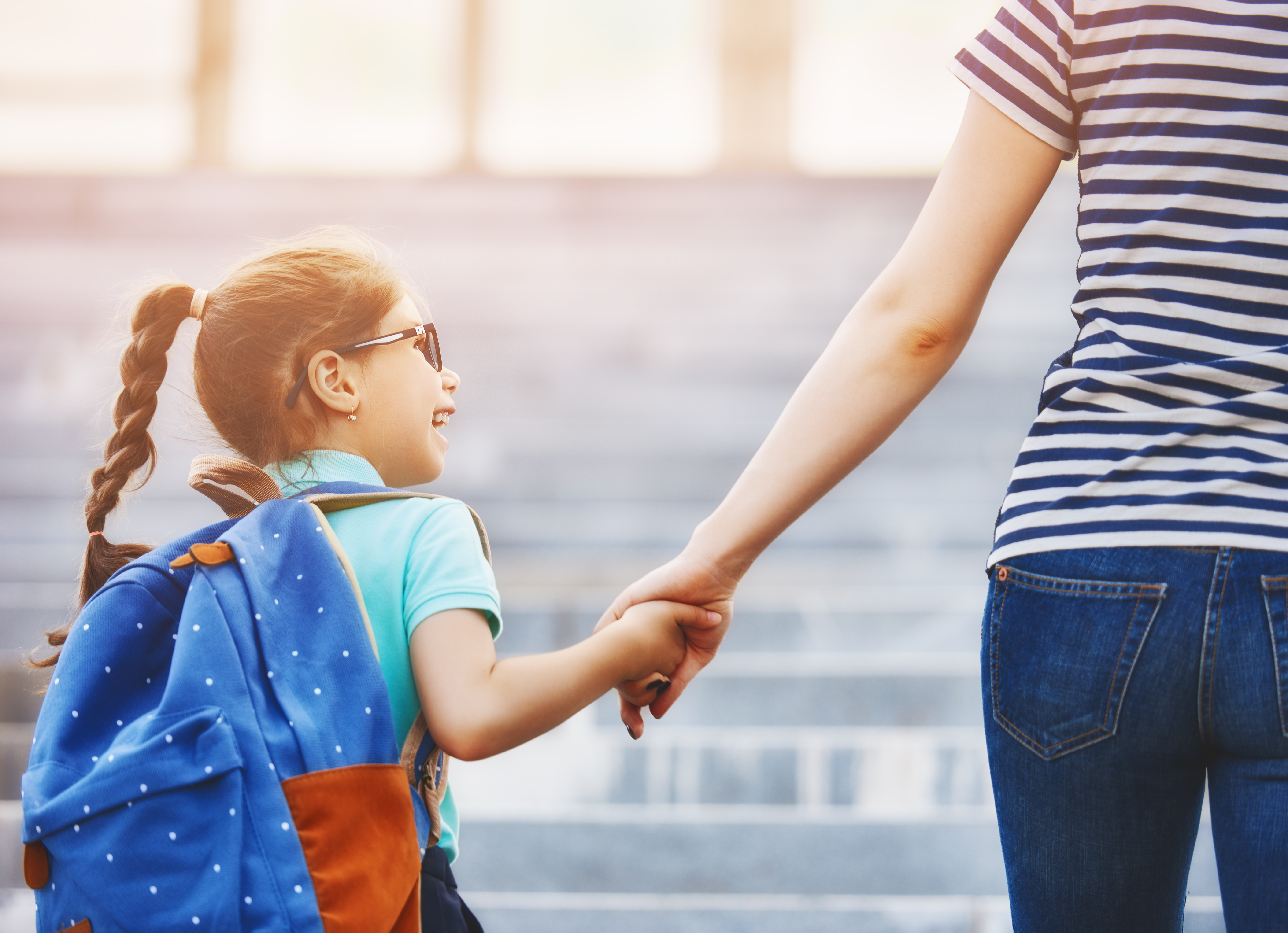 Woman walking little girl to first day of school.
