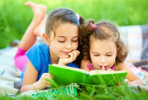 Two little girls reading a book while laying on green grass in the summertime