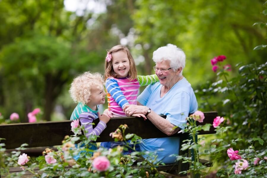 Grandmother and Kids Sitting in a Rose Garden